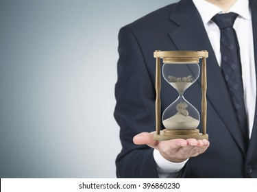 Businessman holding sand glass on palm. Sand running, dollar sign down. Grey background. Concept of time.