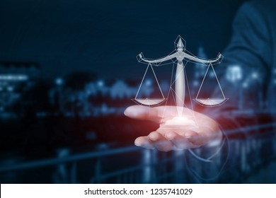 A businessman is holding the scales on his hand at the busy night city centre background. The concept is the legal business affairs principle.