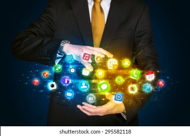 Businessman holding a shining app icon cloud in front of his body