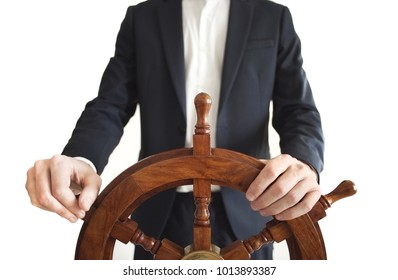 Businessman holding ship rudder.