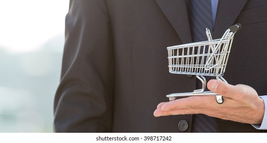 Businessman holding a shopping cart, consumerism background photography