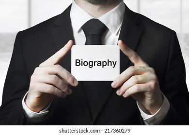 businessman holding sign biography