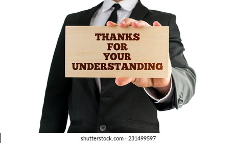 Businessman holding a sign in his hand reading - Thanks For Your Understanding - in appreciation of customers standing by the business in times of stress or during problem solving or interruptions.