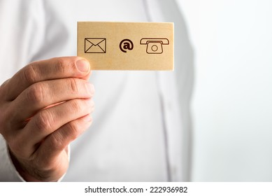 Businessman Holding Small Card with Contact Icons. Over White Background.