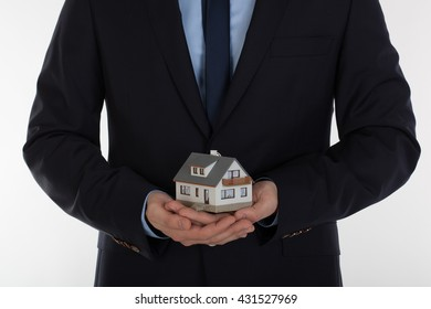 Businessman holding small house in hands. Insurance and security concept.