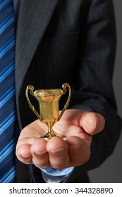 Businessman Holding Small Trophy