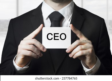 businessman holding small white sign ceo