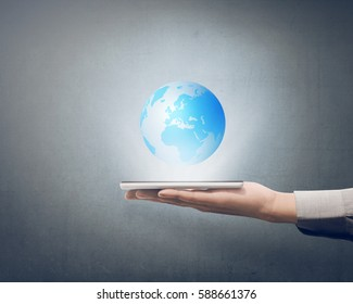Businessman holding smart phone in his hand with globe on it over grey background