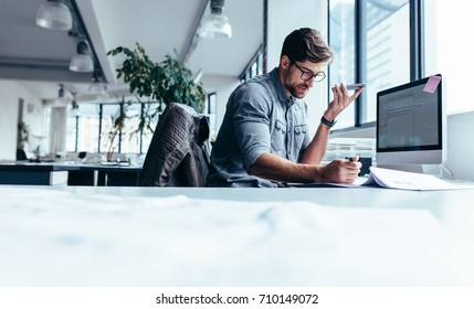 Businessman holding smart phone and working in office. Young caucasian man talking on speaker phone at his desk.