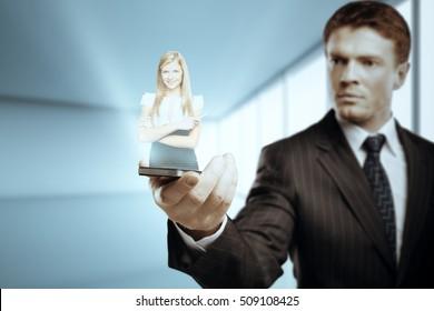 Businessman holding smartphone with female hologram. Digital partnership concept