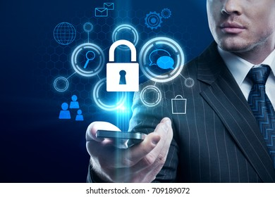Businessman holding smartphone with glowing padlock hologram. Cyberspace concept