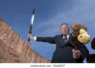 A businessman is holding a sword in an attack posture while riding a stick pony in a desert setting. Horizontal shot.