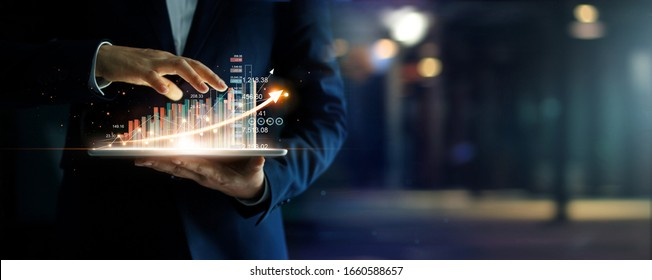 Businessman holding tablet analyzing sales data and economic growth graph chart, Business strategy and planning, Digital marketing and stock market.