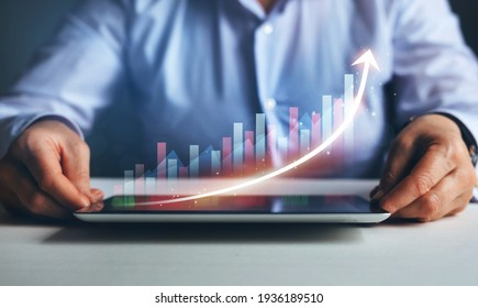 Businessman holding tablet with business growth graph chart. Digital marketing and stock market concept.