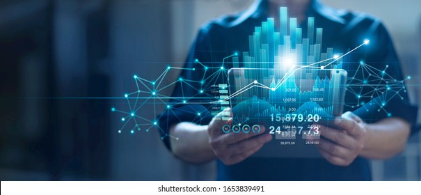 Businessman holding tablet and checking analyzing sales data growth graph chart and stock market on global networking. Business strategy, planning and digital marketing on blue background.