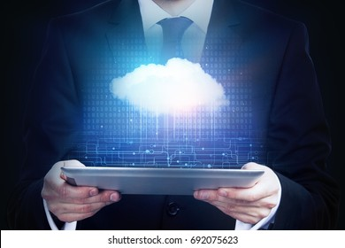 Businessman holding tablet with cloud computing hologram. Technology and innovation concept
