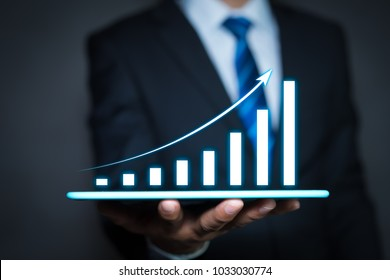 Businessman holding a tablet computer and growing chart floating above digital tablet computer screen. graph corporate growth plan concept