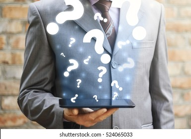 Businessman holding tablet computer with question and cloud question mark. FAQ support questions and answer business help call center concept. Service, Q&A, discussion.