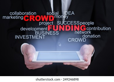 Businessman holding a tablet with crowd funding business concept.