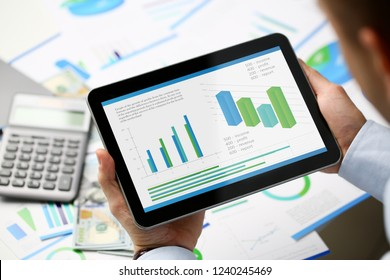 Businessman holding tablet in hands with diagramm on display home office setting. Calculation of family expenses social income population freelance irs situation growth research concept