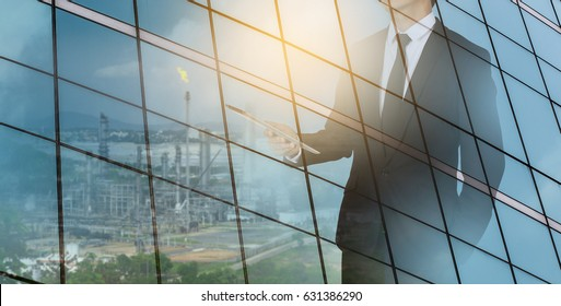 A businessman holding a tablet in his hands with a refinery. communication concept.