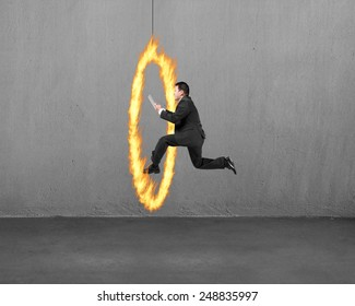 Businessman holding tablet jumping through fire hoop with concrete wall background