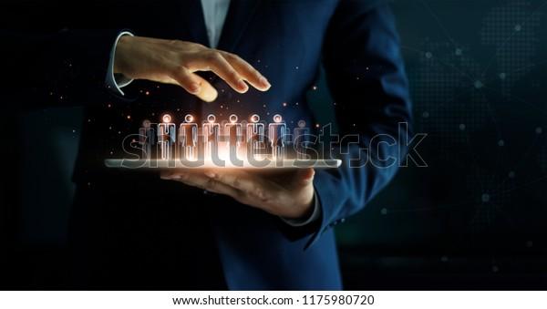 Geschäftsmann, der Tablet-PCs hält und eine Gruppe von Leuten in der Hand hält. Virtuelles Symbol des sozialen Netzwerks. Business Technology Konzept.