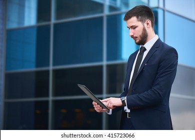 Businessman holding tablet on background of buildings with glass facades