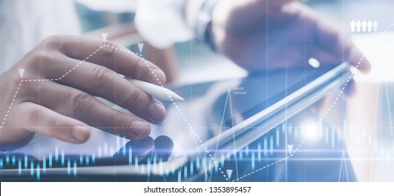 Businessman holding tablet on hand and using electronic pen while working at office.Concept of digital diagram,graph interfaces,virtual screen,connections icon.Wide format