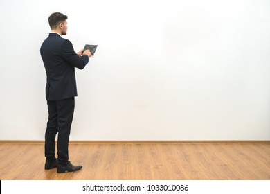 The businessman holding a tablet on the white wall background