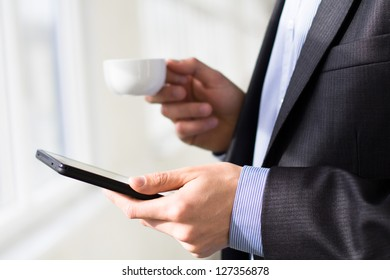 Businessman holding tablet pc and a cup of coffee