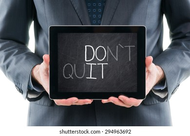 Businessman holding tablet pc with with DO IT made from DON`T QUIT words written on on a chalkboard screen