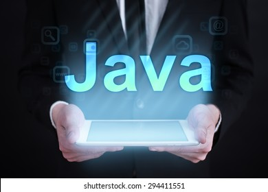 "Businessman holding a tablet pc with ""java"" text on virtual screen. Internet concept. development."