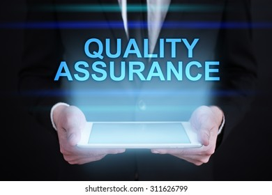 """Businessman holding a tablet pc with """"Quality assurance"""" text on virtual screen. Internet concept. Business concept."""