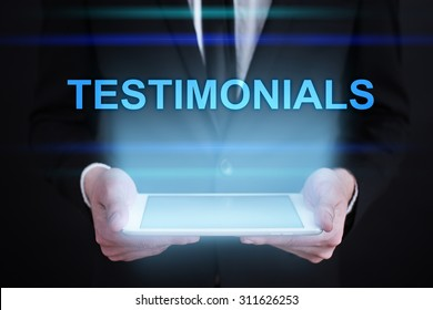 """Businessman holding a tablet pc with """"Testimonials"""" text on virtual screen. Internet concept. Business concept."""