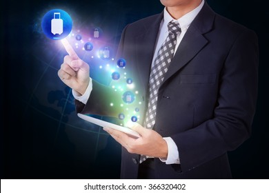 Businessman holding tablet with pressing travel bag sign icon button.
