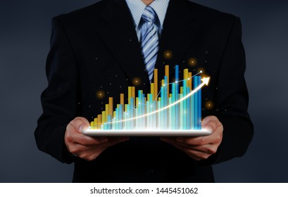 businessman holding tablet report on growth of business virtual chart. business strategic planning conceptual.