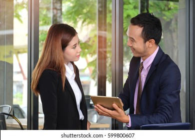 A businessman holding tablet and show business report in electronic file  to businesswoman .The manager discuss about problem with subordinate in the coffee shop  .