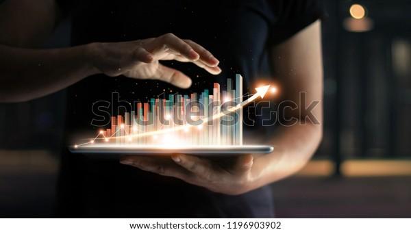 Geschäftsmann, der Tablet hält und ein wachsendes virtuelles Hologramm von Statistiken, Diagrammen und Diagrammen mit Pfeil nach oben auf dunklem Hintergrund zeigt. Aktienmarkt. Unternehmenswachstum, Planing und Strategiekonzept.