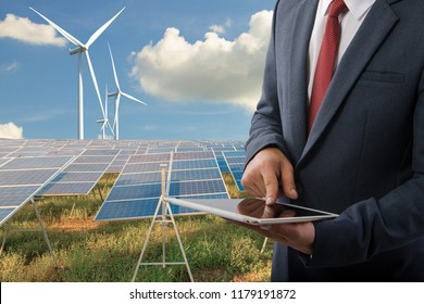 Businessman holding a tablet at Solar panels with wind turbines  blue sky with clouds background and (solar cell)  create the clean electric power Business Concept.