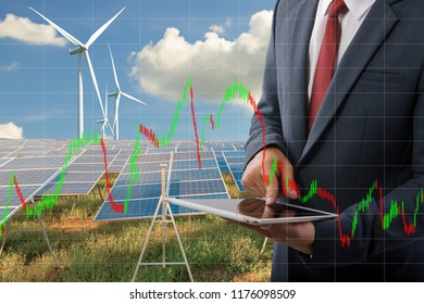 Businessman holding a tablet and Stock graph at Solar panels with wind turbines  blue sky with clouds background and (solar cell)  create the clean electric power Business Energy investment Concept.