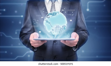 Businessman holding a tablet which is showing a hologram of the Earth. Digital imaging of the planet. International communication and globalization. Expanding business dealings all over the world.