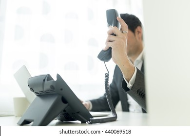 Businessman holding a telephone receiver as if about to place it on base or just has picked it up sitting at his white office desk.