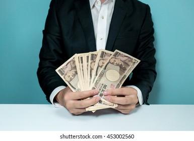 Businessman holding a lot of ten thousands yen