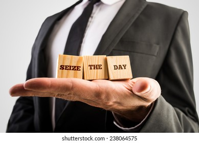 Businessman holding three wooden cubes or building blocks in the palm of his hand with the words - Seize the day - in a motivational and inspirational message.
