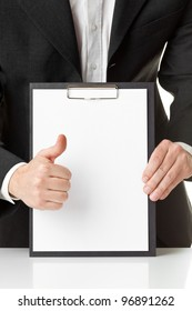 Businessman holding thumb up in front of blank clipboard with copyspace