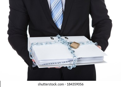 Businessman holding a top secret confidential file locked up with a chain and padlock to prevent unauthorized access  isolated on white