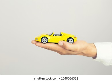Businessman holding a toy car, isolated background