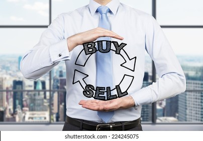 Businessman is holding a trading concept in his hands. City view office.
