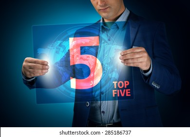 Businessman holding a transparent screen with an inscription a top five. Business, technology, internet and networking concept.